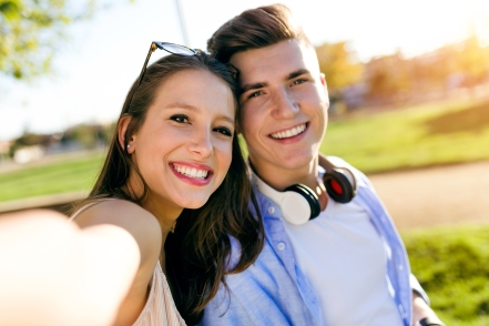 Beautiful young couple taking a selfie in the park.